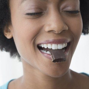 Close up of African American woman eating square of chocolate