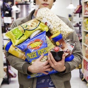Young man holding armful of junk food
